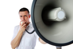 Portrait of a man roaring loudly into megaphone over white background